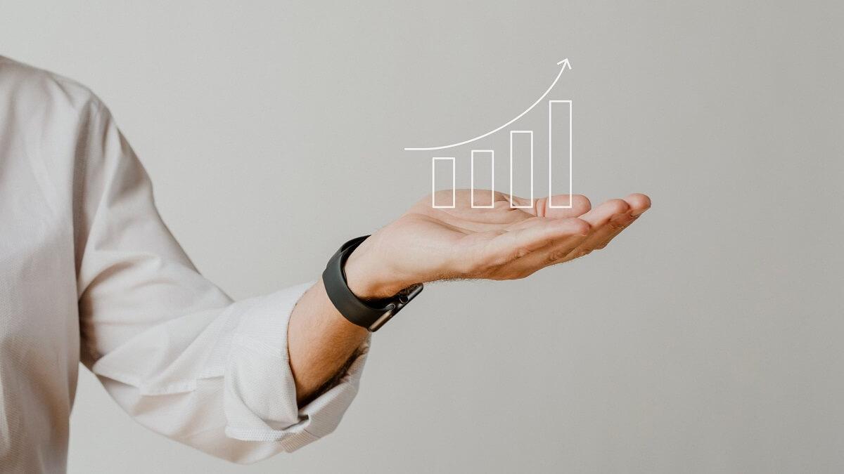 mužská ruka ukazuje rastúcu krivku