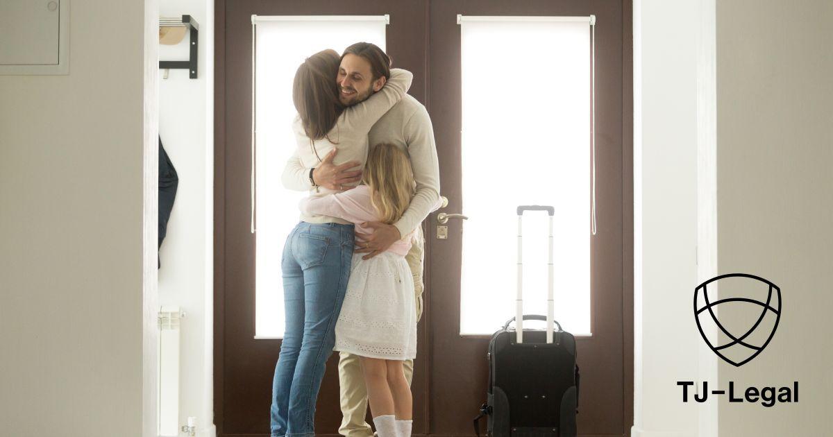 muž sa lúči pri dverách s rodinou