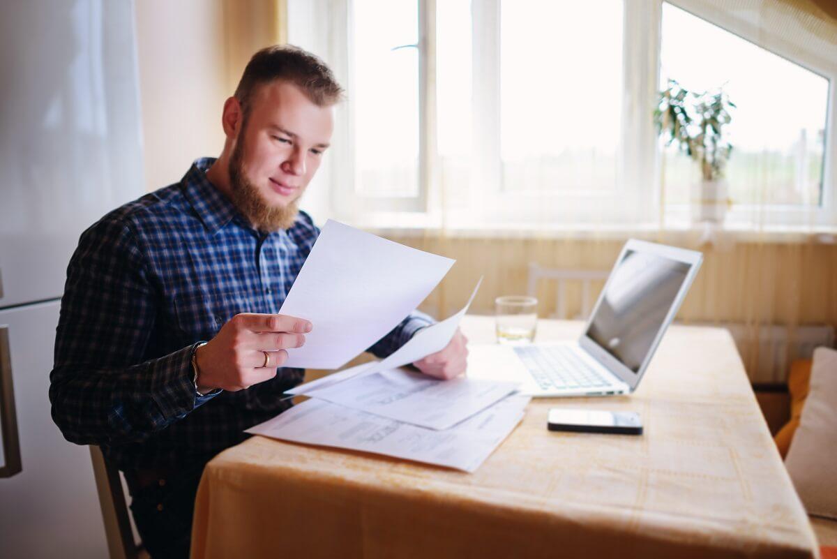muž číta nemeckú výplatnú pásku